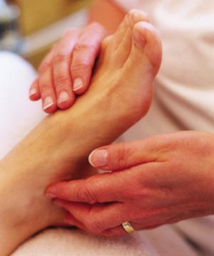 Patient receiving reflexology whilst student 'reads' the feet during treatment