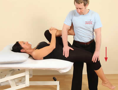 The therapist passively extends the hip to lengthen the psoas, assisted by gravity.