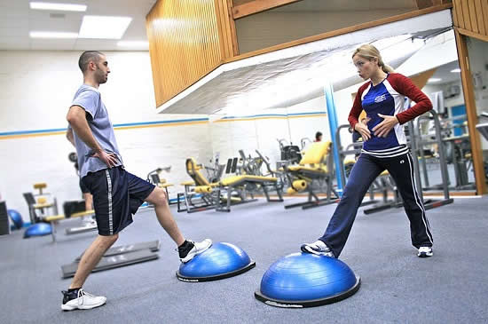Two_people_in_a_gym_using_BOSU_ball
